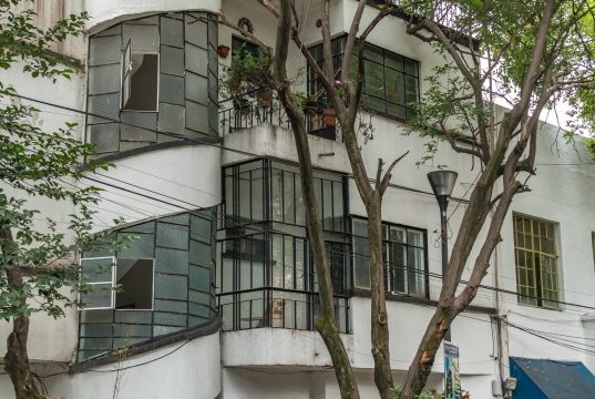 Photo of second and third floors of house with cylindrical glass and concrete external staircase.