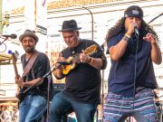 Photo of three men playing and singing on an outdoor stage.