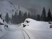 Photo of railroad tracks curving through a cut in a snow-covered mountainside.