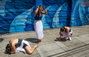 Photo of three women performing an interpretive dance in front of a large mural.