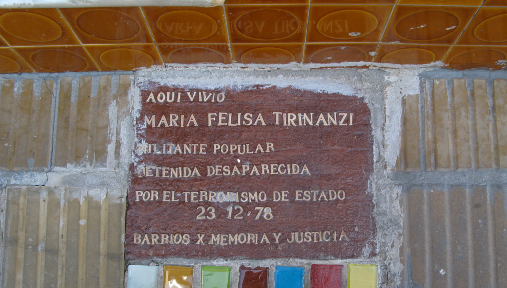 Photo of sidewalk marker, made of colored tiles in a line under a brown background with white letters.