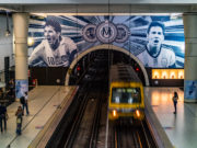 Photo of wide shot of train entering subway station interior, with one large wall painted with scenes of soccer star Lionel Messi.