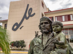Photo of statue of Che Guevara in front of building with large logo of his signature.