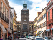 Photo of tall clock tower in front of market building.