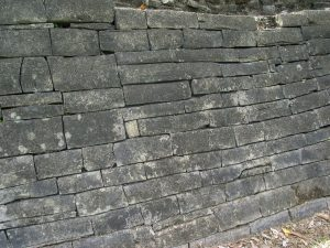 Photo close up of stacked and fitted stones making up a wall.