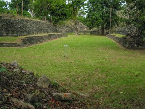 Photo of grass covered field with matching low stone structures on each side.